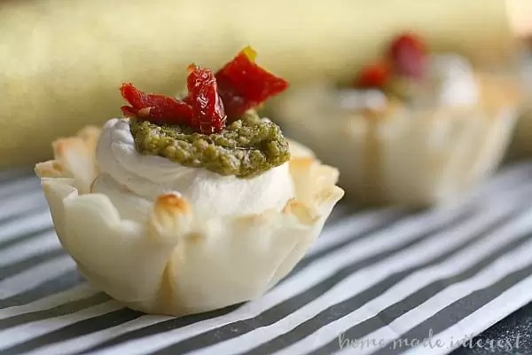 These Sun Dried Tomato, Pesto, and Garlic bite-size appetizers are perfect for parties. Creamy cheese in a phyllo cup, topped with sun dried tomato, pesto.