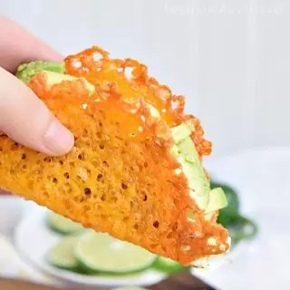 Hand holding a keto taco made with a cheese taco shell