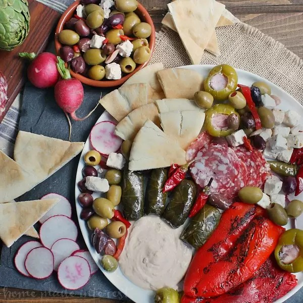 This easy antipasto platter is going to be a hit at your next party. A mediterranean antipasto platter filled with peppers, dolmas, meats, olives, and cheeses, served with flavored greek yogurts and pita bread, makes the perfect appetizer for a party.