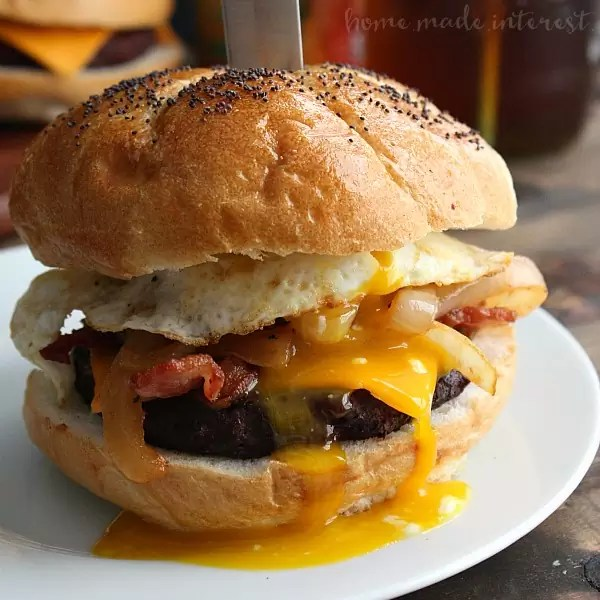 This grilled Bacon BBQ Meatloaf Burger is a tender and juicy burger twist on a classic comfort food, meatloaf! The burger patties are made with a delicious meatloaf base basted in BBQ sauce and topped with crispy bacon and a fried egg! An awesome grilled burger recipe that is perfect for summer, 4th of July, and Labor Day cookouts!