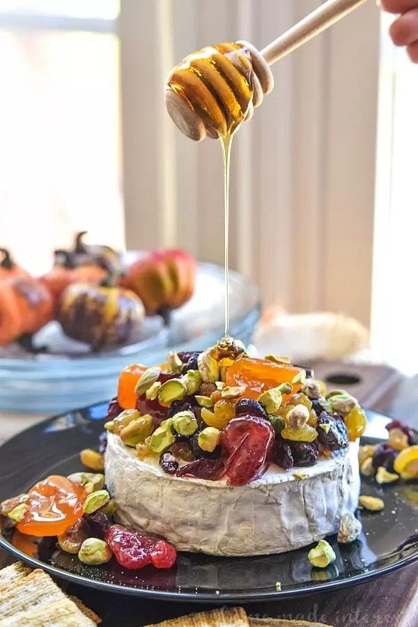 This Dried Fruit and Pistachio Baked Brie is an elegant and delicious appetizer recipe that is perfect for Thanksgiving, Christmas, and New Year's Eve. The dried fruit and pistachios are coated in a sweet drizzle of honey and placed on top of the melted brie to be served with bread and crackers.