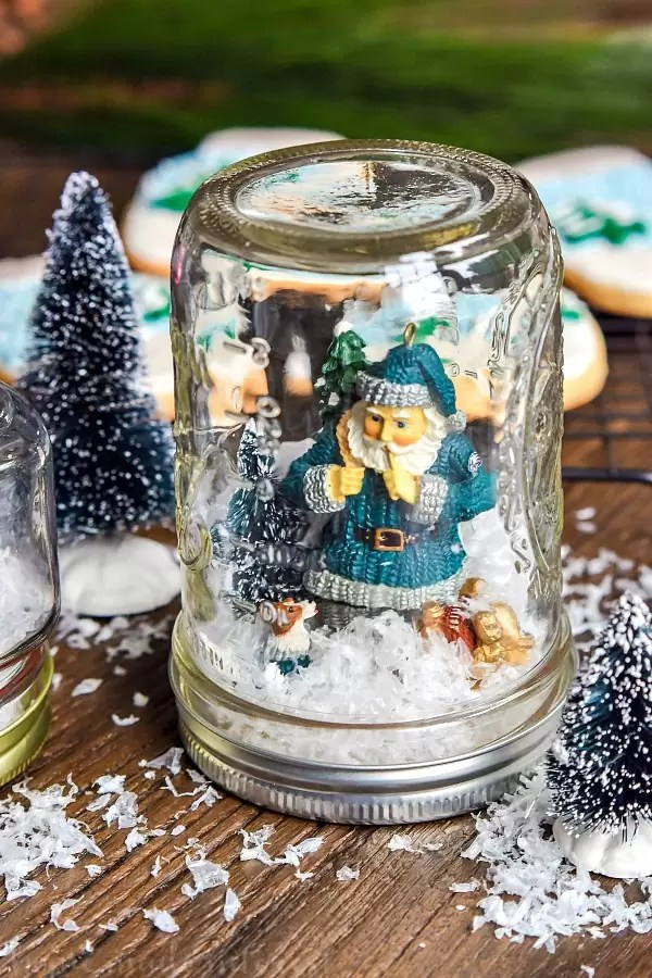We have a simple tutorial for DIY Waterless Snow Globes made with mason jars. Mason jar snow globes are so much fun and these don't require any water. We even made matching snow globe cookies that we decorated and served to the kids while we worked on our DIY snow globes!