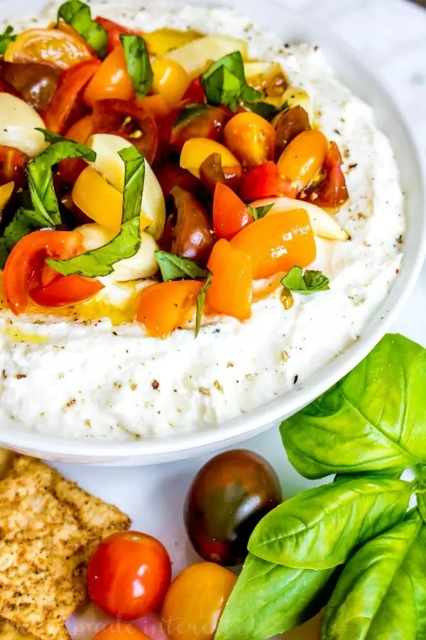 Whipped Goat Cheese and Tomato Dip | This is an easy appetizer recipe that is perfect for summer parties. Whipped Ricotta Tomato Dip combines ricotta cheese and goat cheese with fresh herbs and summer vegetables to make a light, bright summer appetizer recipe that everyone can enjoy. This light cheese dip is a cold appetizer recipe that is perfect for taking to a party.