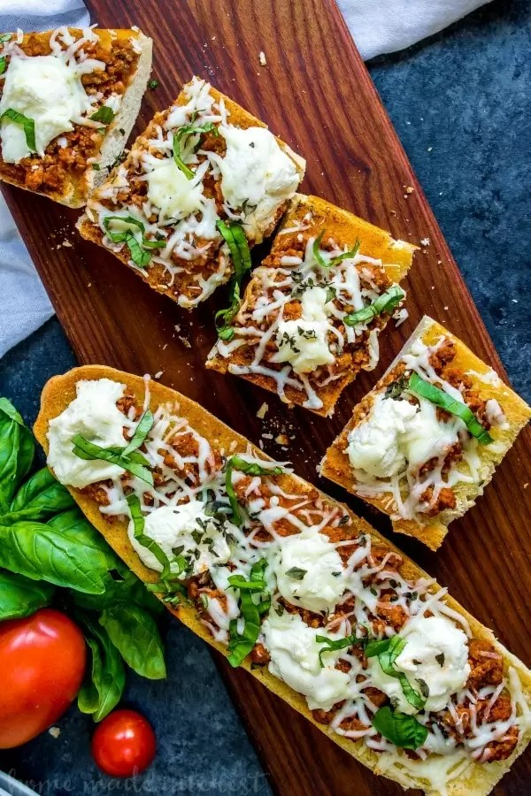 whole lasagna french bread pizza with slices next to it on a wooden board