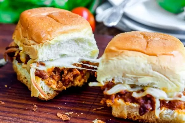 Lasagna sliders together with cheese stretching between them.