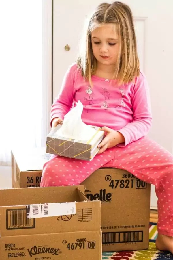 girl sitting on box with tissue box