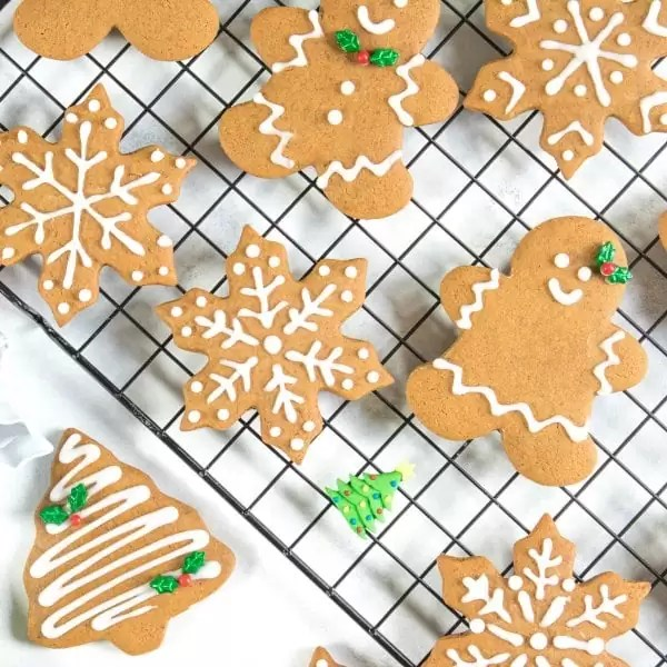 Soft gingerbread cookie recipe with gingerbread men, gingerbread women, Christmas trees, and snowflakes baked and iced with royal icing