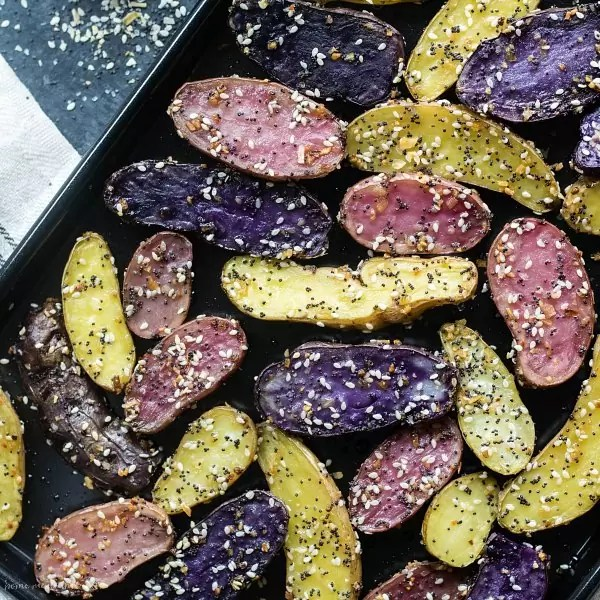 Sheet pan full of purple, pink, and yellow Everything Bagel Roasted Fingerling Potatoes