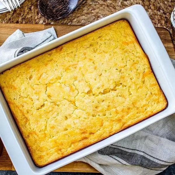 Creamed corn casserole in a white casserole dish.