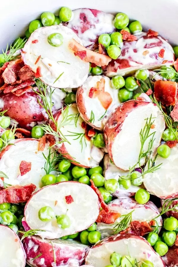 English Pea and Potato Salad with large crumbles of bacon, bright green peas, and creamy vinaigrette on red potatoes