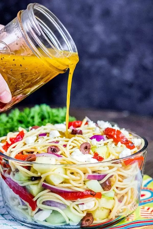 dressing poured over Greek Spaghetti Salad