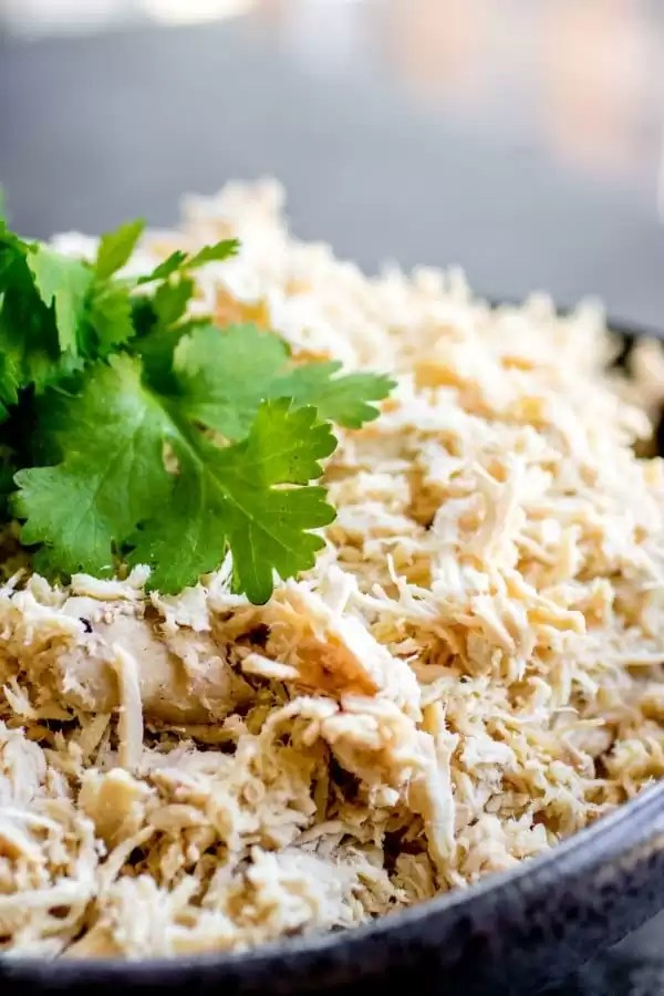 shredded chicken in a bowl topped with parsley