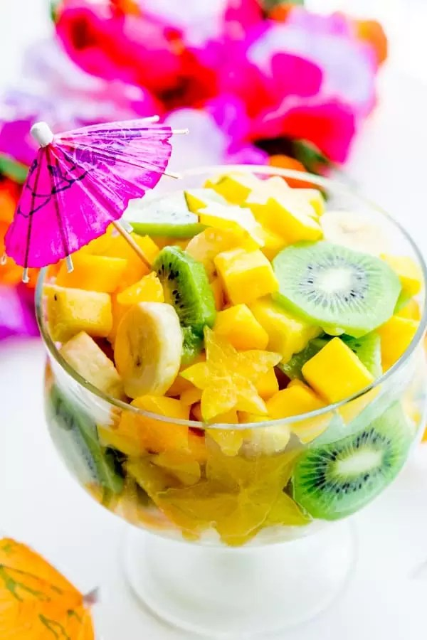 Pina Colada Tropical Fruit Salad served in a large glass bowl with a drink umbrella