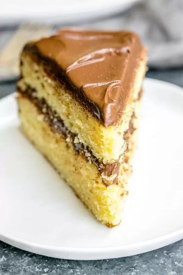 A big slice of yellow butter cake with chocolate frosting on a white plate