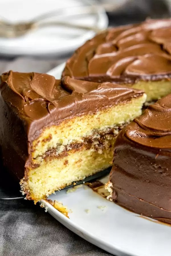 Cutting a slice of Yellow Butter Cake with chocolate frosting
