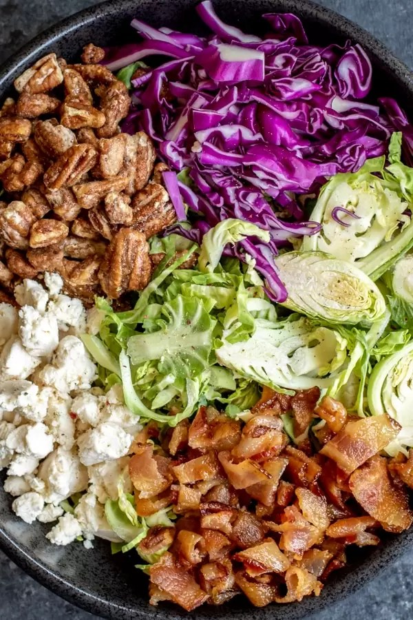 Ingredients in Brussels Sprout Salad bacon, goat cheese, candied pecans, brussels sprouts, red cabbage