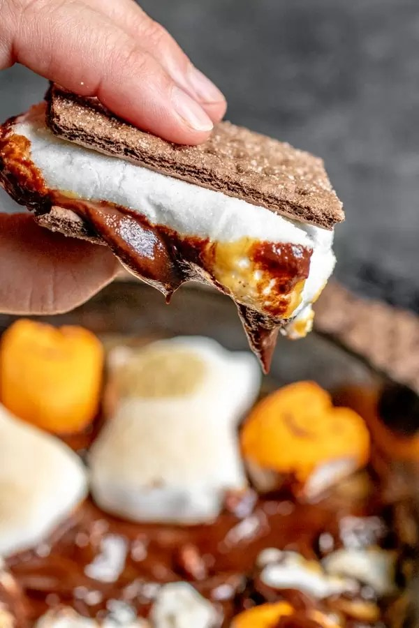 holding s'more made with Halloween S'mores Dip