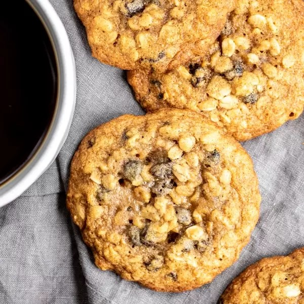 oatmeal raisin cookies sitting next to a cup of coffee
