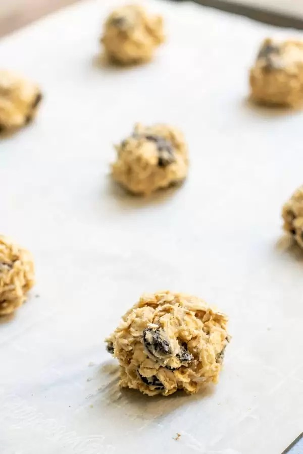 balls of chewy oatmeal raisin cookie dough sitting on a baking sheet