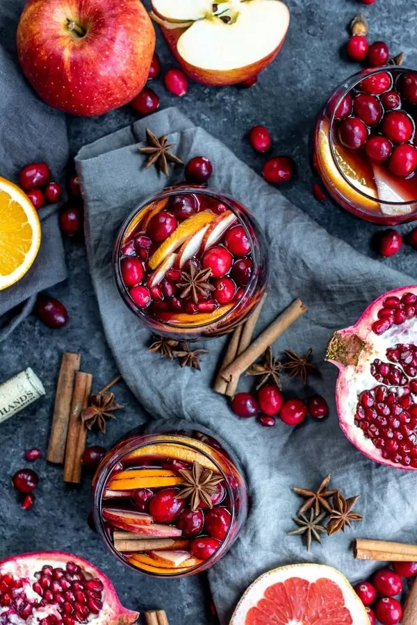 Winter Red Wine Sangria in three stemless wine glasses filled with oranges, grapefruits, apples, cranberries, pomegranate seeds and spices.