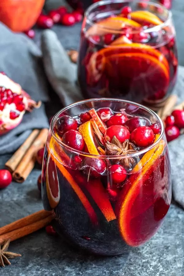 Winter Red Wine Sangria surrounded by pomegranate seeds, and whole spices