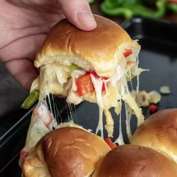A delicious chicken cheesesteak slider with provolone cheese oozing out