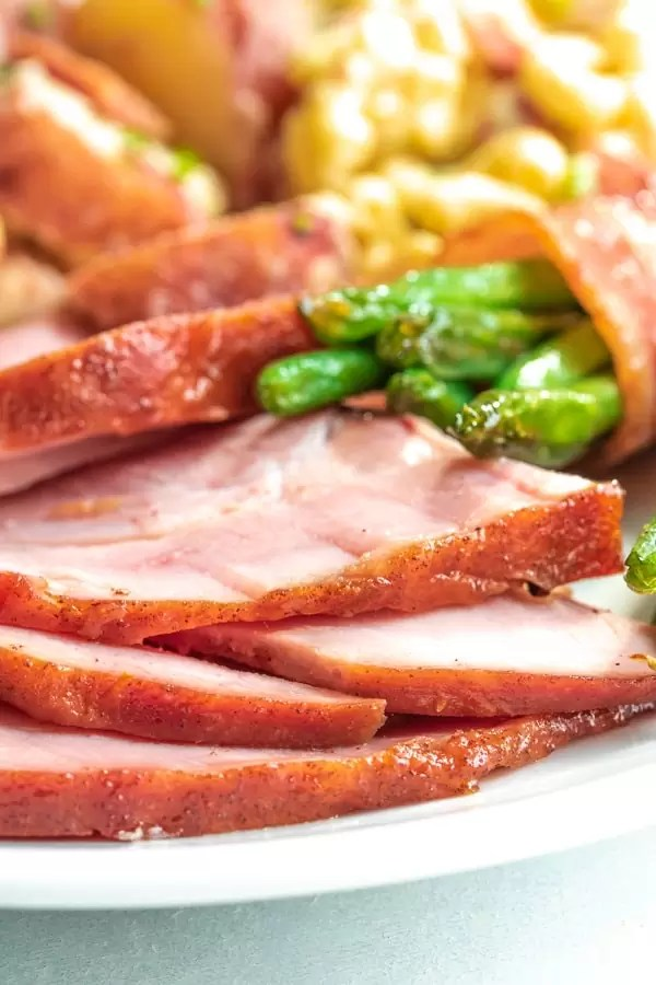 Honey glazes ham on a plate with sides