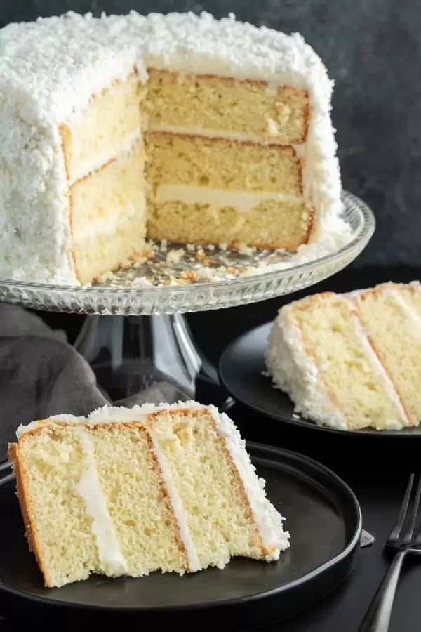 Coconut cake with two slices of cake cut and on plates