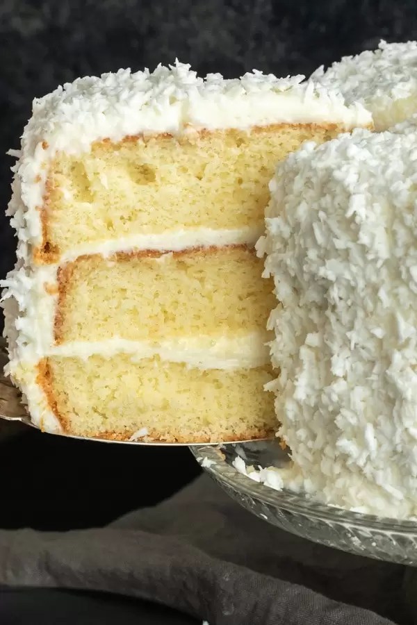 Slice of coconut cake being cut from a three layer coconut cake