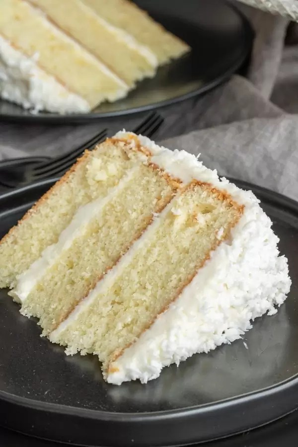 A slice of three layer coconut cake with fresh coconut
