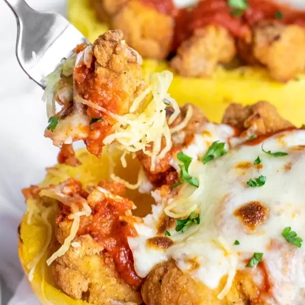A fork digging into chicken parmesan roasted spaghetti squash