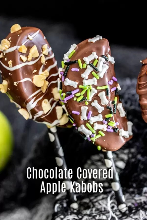 These Chocolate Covered Apple Kabobs are an easy idea for your Halloween party. Chocolate covered apple slices on a stick make serving candied apples super easy. Decorate them with dark chocolate, milk chocolate, and white chocolate, and top with your favorite candies. It's a fun fall dessert or Halloween dessert recipe. #dessert #apple #chocolate #halloweenrecipes #halloweenparty #homemadeinterest