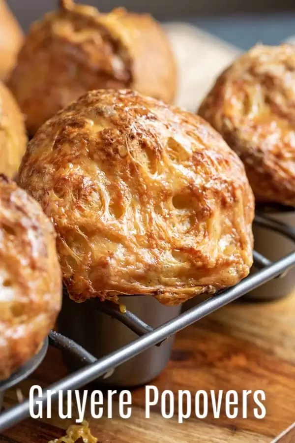 These easy Gruyere Popovers are a fluffy, cheesy popover recipe that make a great addition to Thanksgiving dinner or Christmas dinner! These cheesy popovers are a savory bread recipe that is easy to make and always impresses guests! #bread #popovers #cheese #thanksgiving #christmas #rolls #baking #homemadeinterest