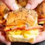 Hands holding a Ham Egg and Cheese Breakfast Slider