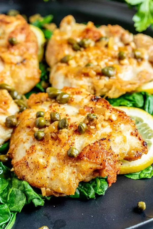 Keto Chicken Piccata on a bed of spinach and fresh lemons