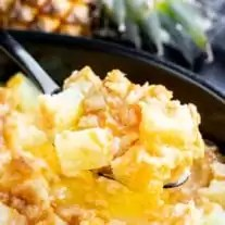 Serving a scoop of baked pineapple casserole