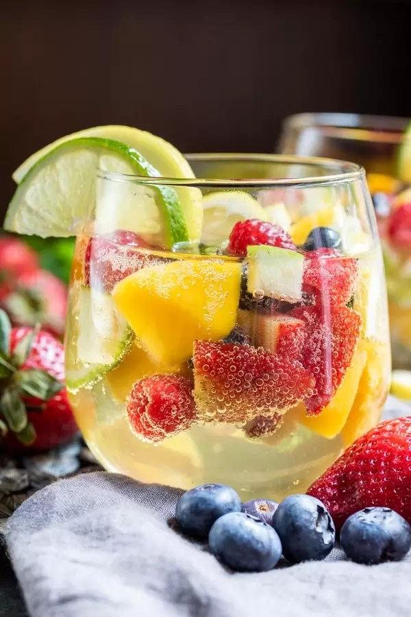 Side shot of Summer Moscato Sangria in stemless wine glasses filled with summer fruit