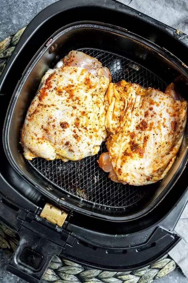 raw Air Fryer Chicken Thighs in air fryer basket