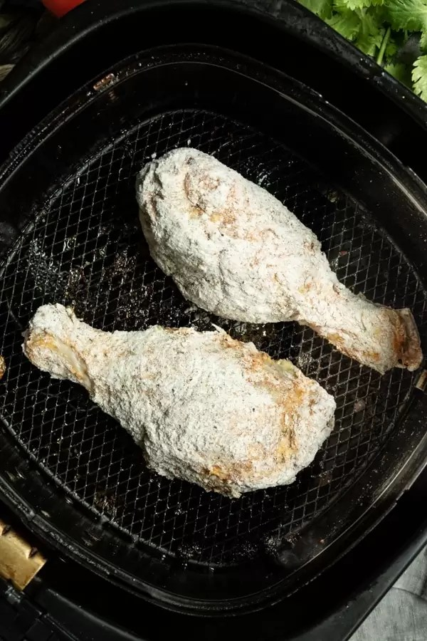 Raw chicken coated in flour and placed in the air fryer