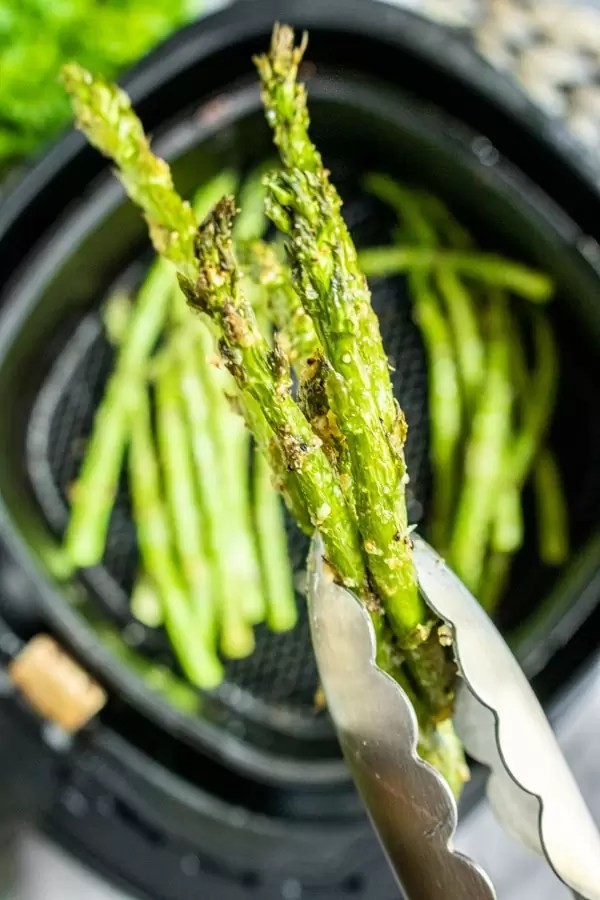 tongs holding Air Fryer Asparagus