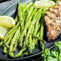 Air Fryer Asparagus on a black plate with chicken