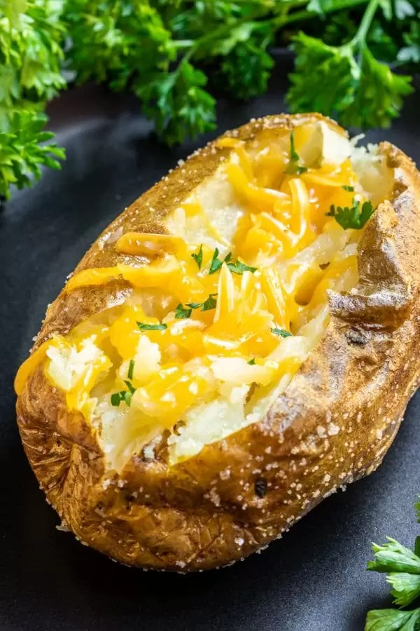 crispy Air Fryer Baked Potato on plate with melted cheese on top