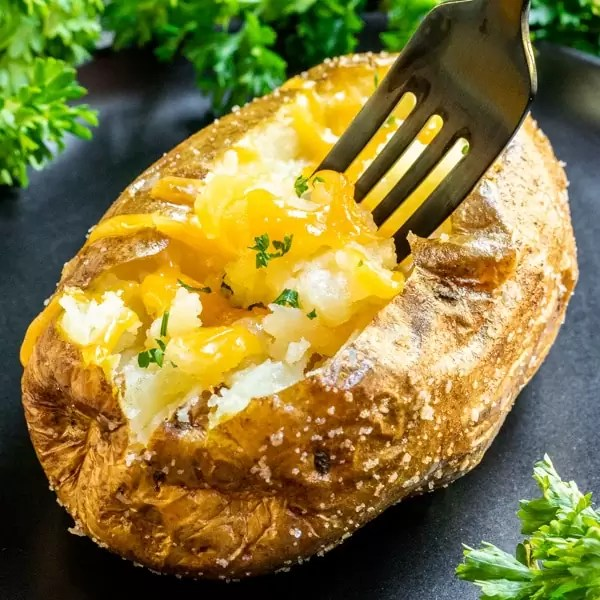 Air Fryer Baked Potato with fork and cheese