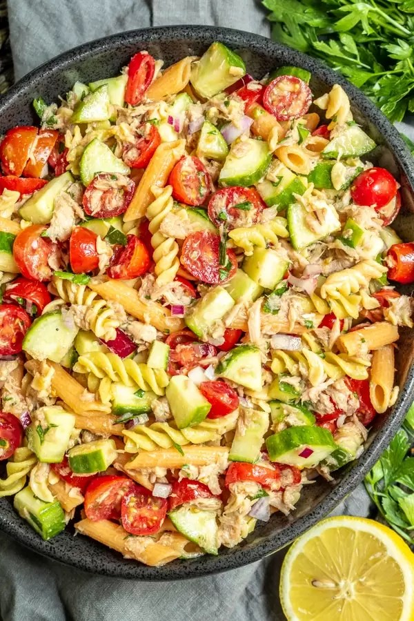 big bowl of Tuna Pasta Salad with half a lemon and parsley