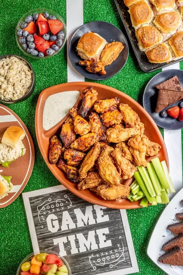 Top down view of football party food table with chicken wings in the center, fresh fruit, and sliders.