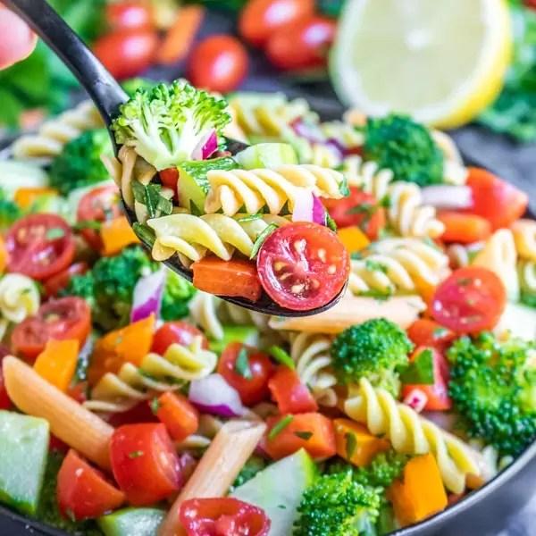 spoonful of vegan pasta salad over a bowl of vegan pasta salad