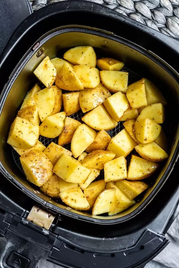 air fryer basket with raw cubed potatoes