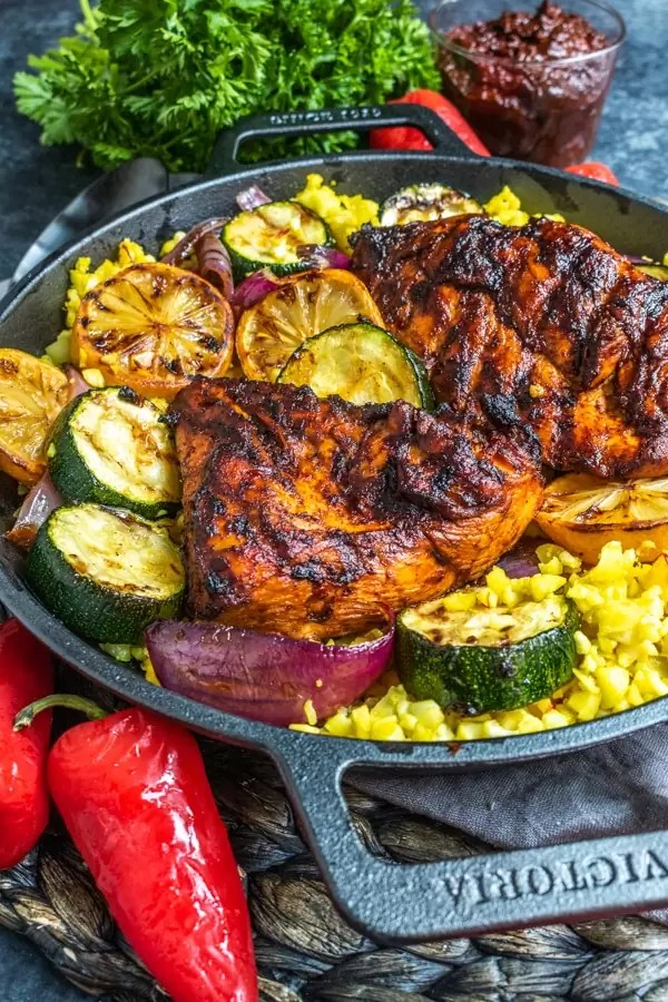 Side shot of grilled harissa chicken in a black dish