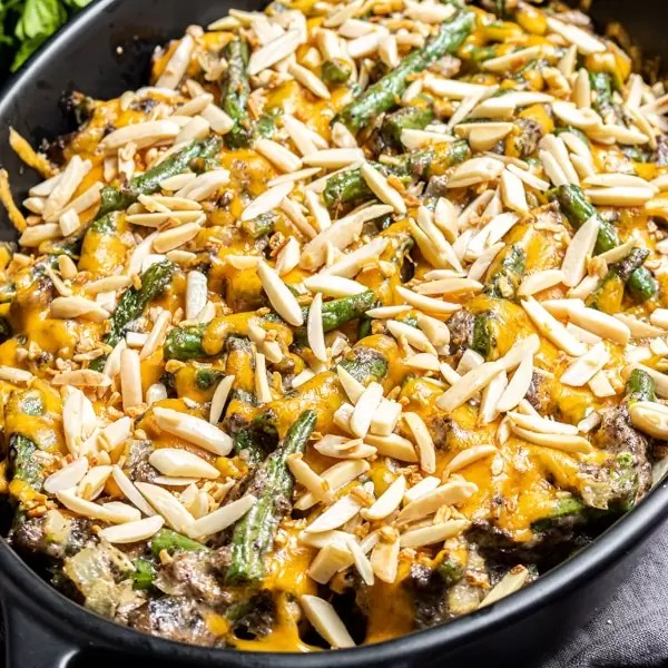 black platter with Keto Green Bean Casserole with almond slivers on top