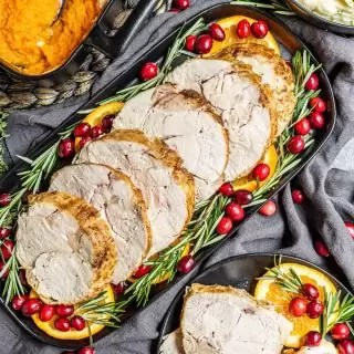 platter of Instant Pot Turkey Breast garnished with orange slices and fresh cranberries
